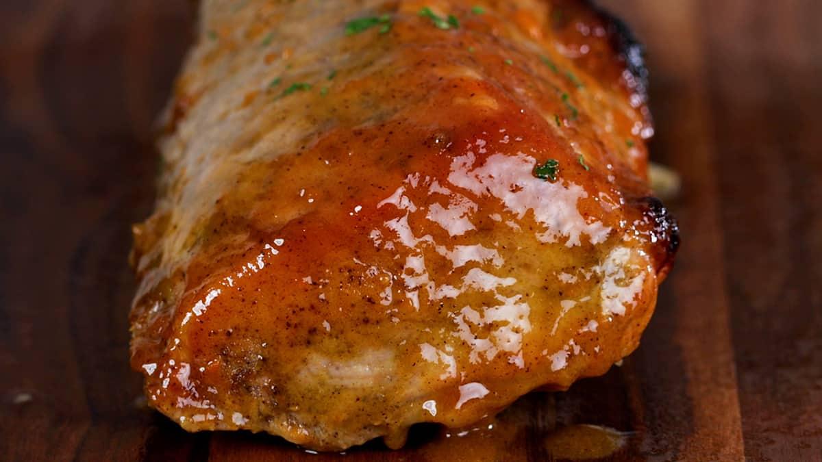 glazed pork roast resting on a wooden surface