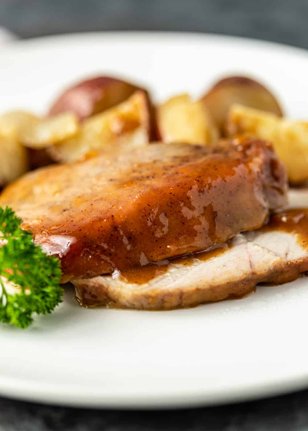 slices of glazed pork loin and roasted potatoes on a white plate