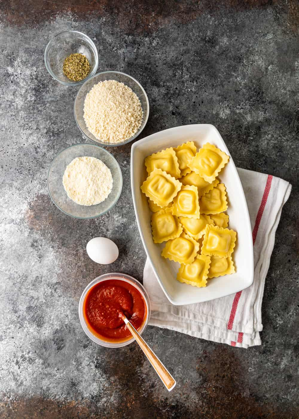 individual bowls with cheese ravioli recipe ingredients on a counter with a dish towel