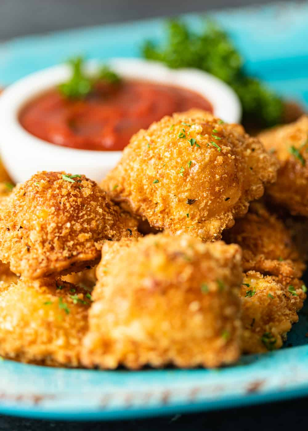 close up of deep fried ravioli with a bowl of marinara and fresh parsley in the background
