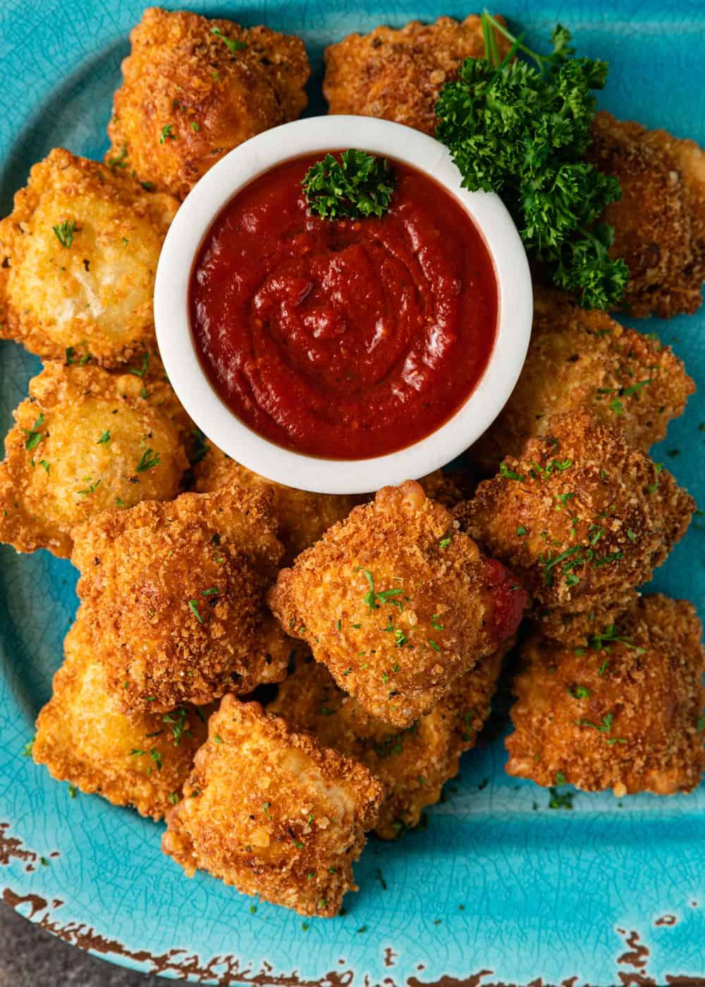 overhead photo: blue platter of crispy fried cheese ravioli appetizers with marinara sauce