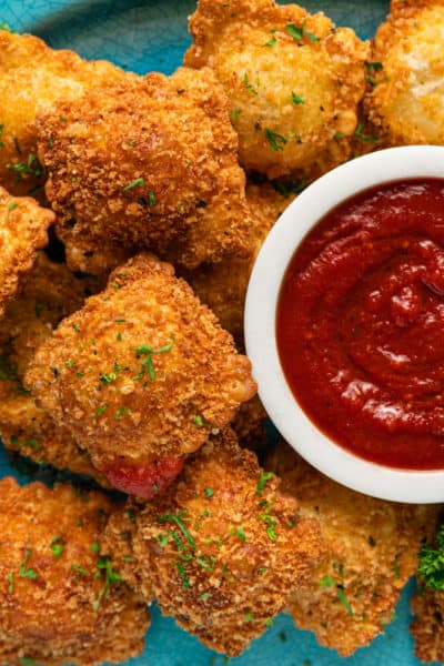 overhead photo of a white bowl of marinara surrounded by fried breaded ravioli and fresh parsley on a blue platter