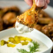 baked crispy chicken drumette being dipped into dill dipping sauce