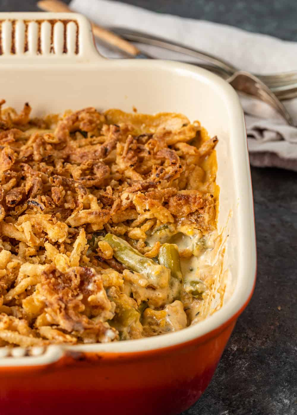 baking dish with easy green bean casserole on a counter next to a cloth napkin and silverware