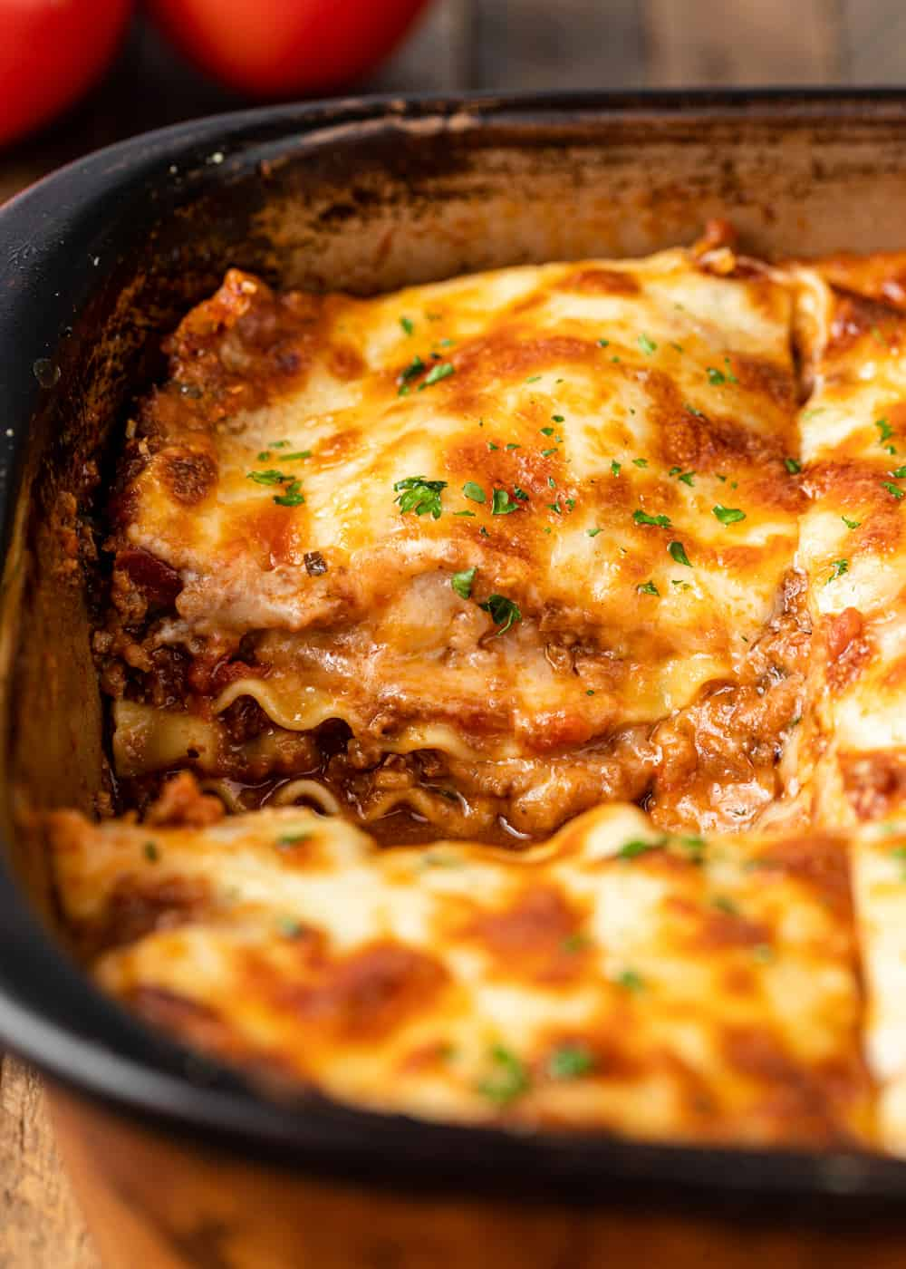 close up of a pan of lasagna bolognese with a missing slice