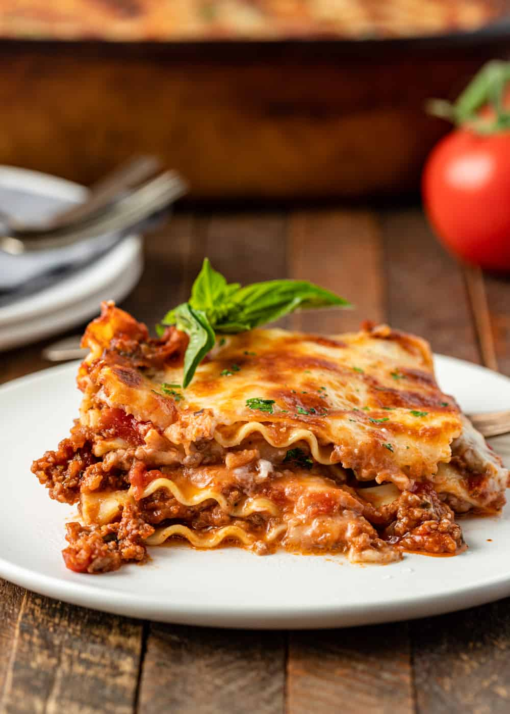 serving of lasagna bolognese on a white plate with a baking dish, tomato, and additional plates and utensils in the background