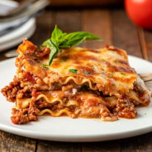 a slice of homemade lasagna on a white plate garnished with fresh basil leaves