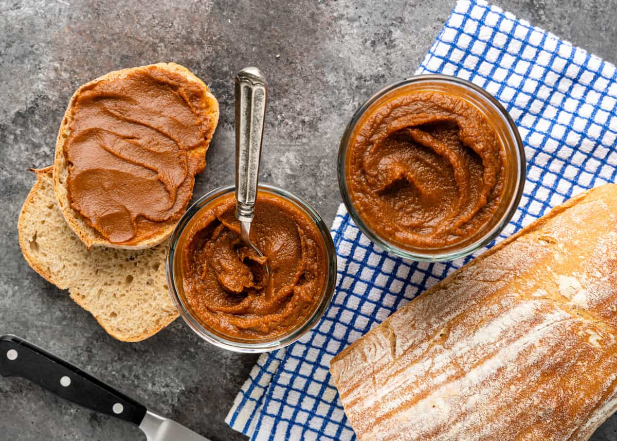 overhead of bread and jars of pumpkin spread on a counter with a checkered towel and knife