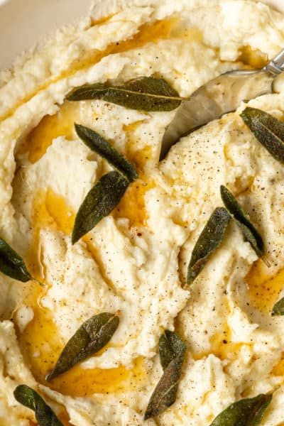 overhead photo: bowl of brown butter mashed potatoes with fried sage leaves