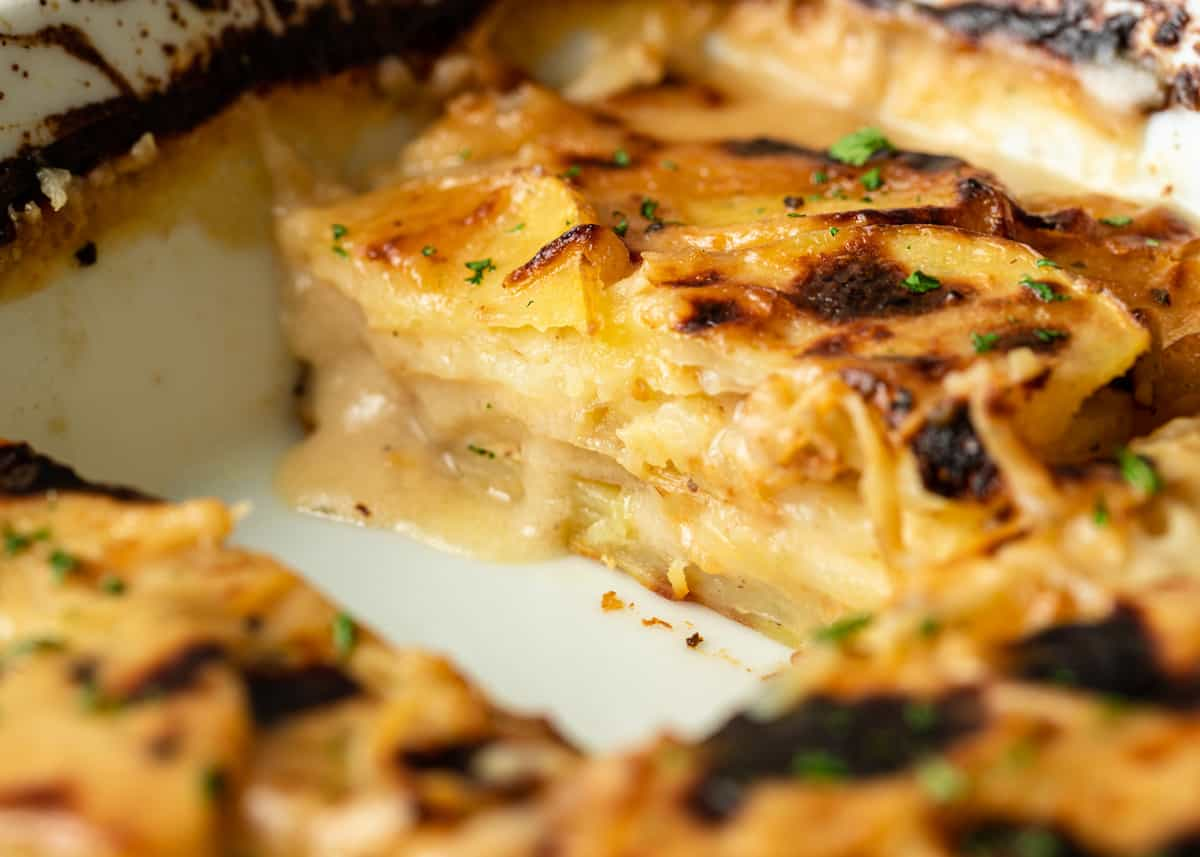 scalloped potatoes in a baking dish with a slice missing