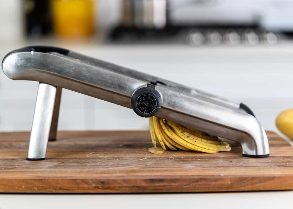 sliced potatoes beneath a mandolin slicer on a wooden cutting board