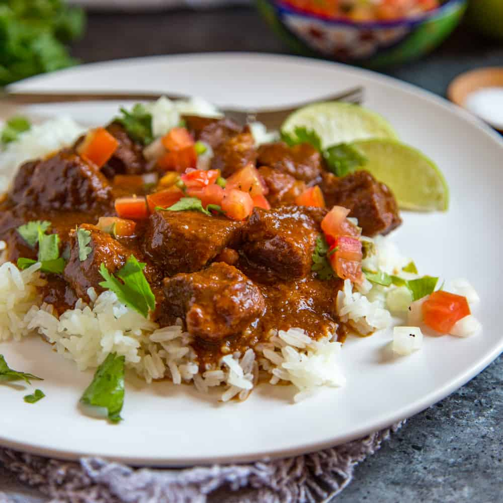 carne adovada served over rice on a white plate
