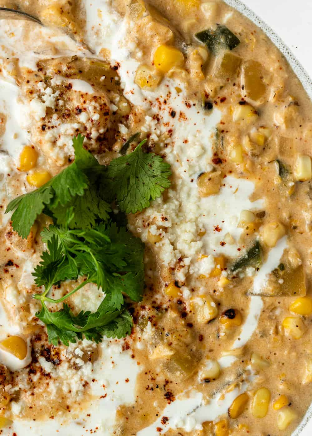 close up of poblano corn chowder topped with Mexican crema, cilantro, and spices
