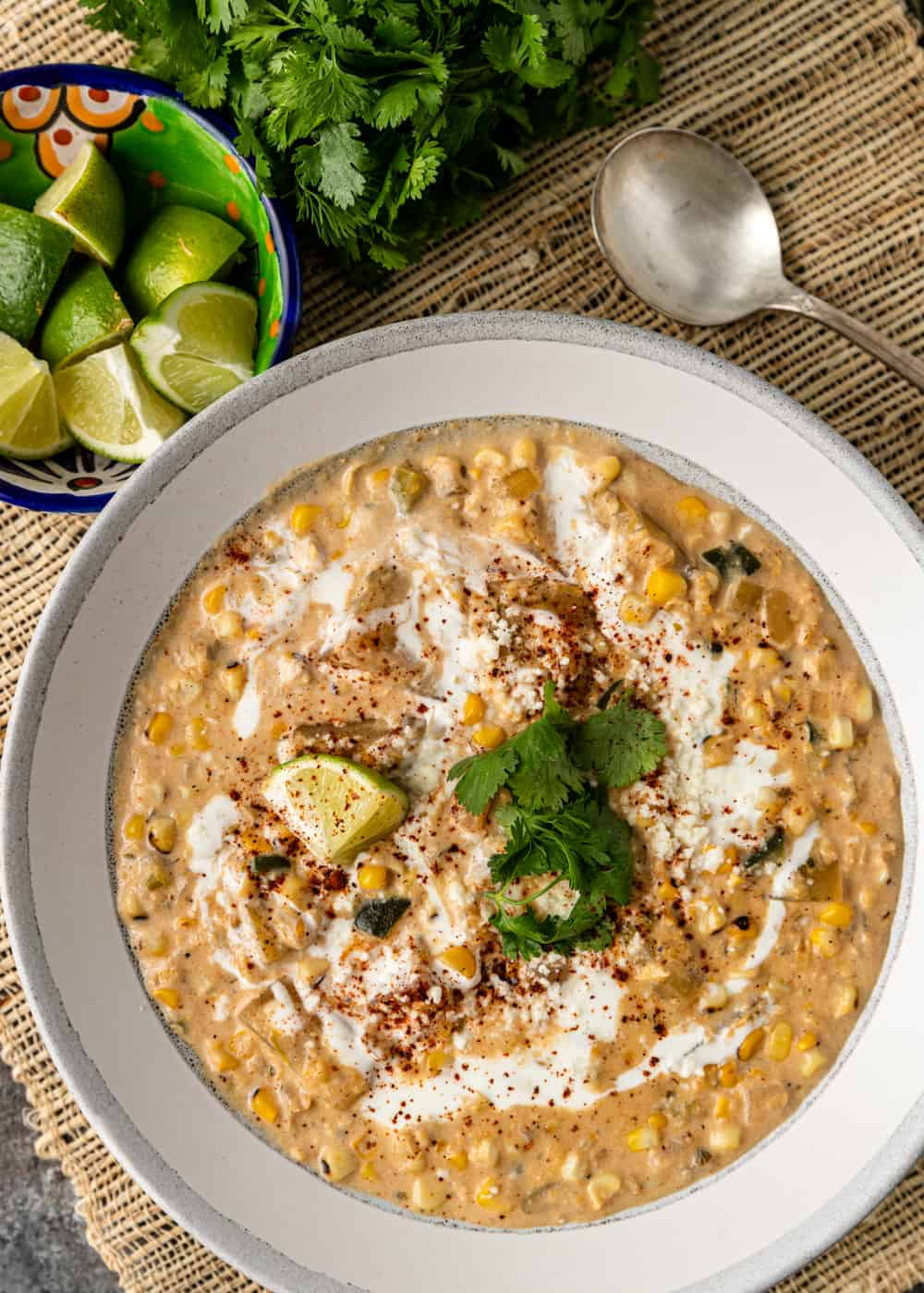 poblano corn chowder in a white bowl next to lime wedges, cilantro, and a spoon