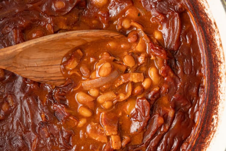 wooden spoon stirring pot of baked beans with bacon