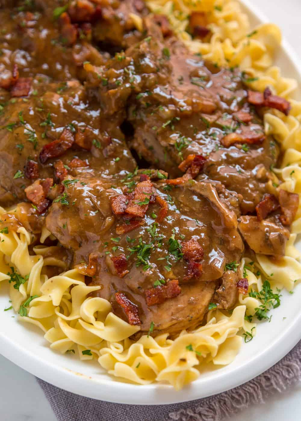 A close up of pork chops with bacon gravy on noodles