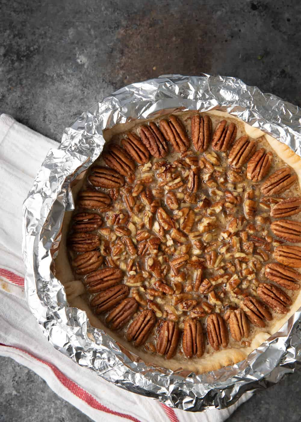 overhead image: pecan pie with maple syrup in a crust wrapped with aluminum foil