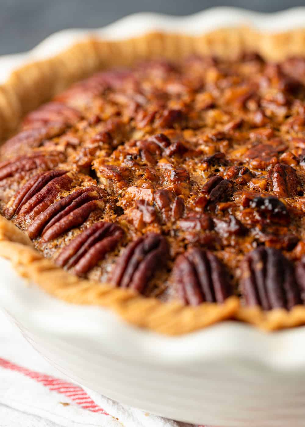 close up of toasted pecans garnishing the outside of a pie