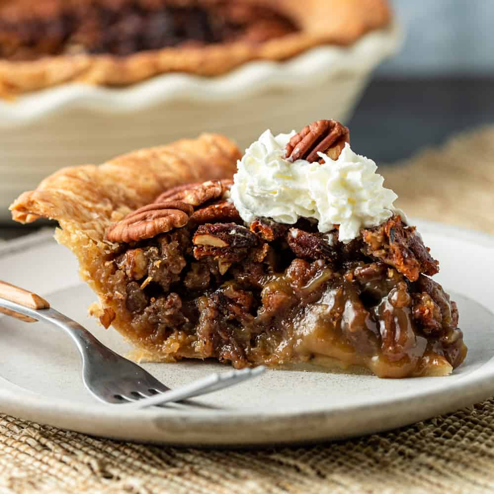 plated slice of southern pecan pie topped with swirl of whipped cream and a pecan