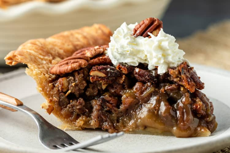 side view: plated sliced of Thanksgiving pie topped with whipped cream and pecans