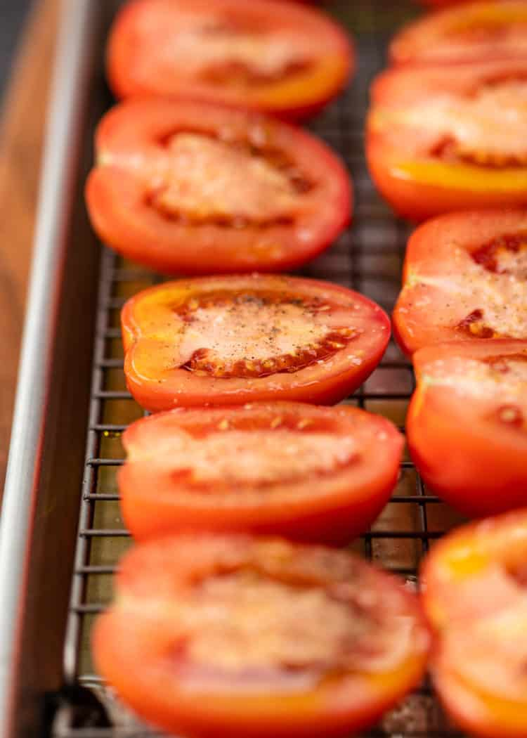 close up of ripe plum tomatoes sliced in half on a baking sheet