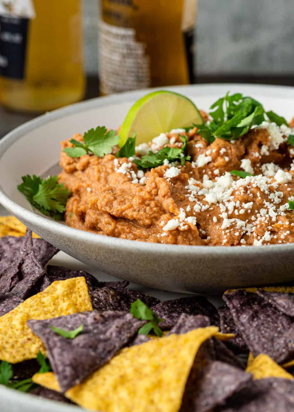 close up photo: bowl of homemade refried pinto bean dip surrounded by corn tortilla chips