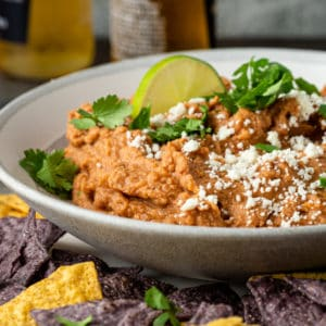 easy refried bean dip garnished with crumbled Mexican cheese in white bowl