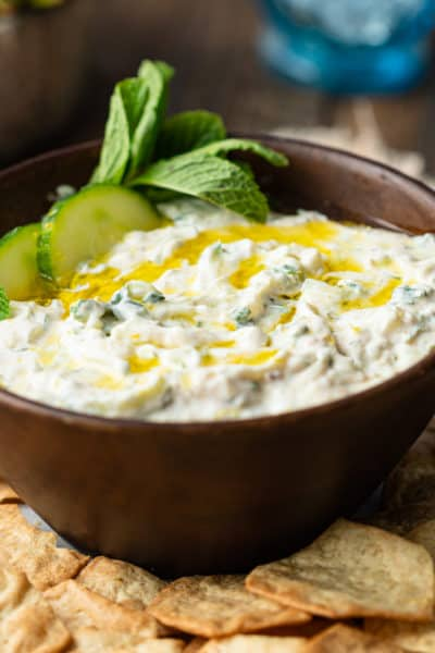 authentic tzatziki in brown bowl garnished with fresh mint and cucumber slices