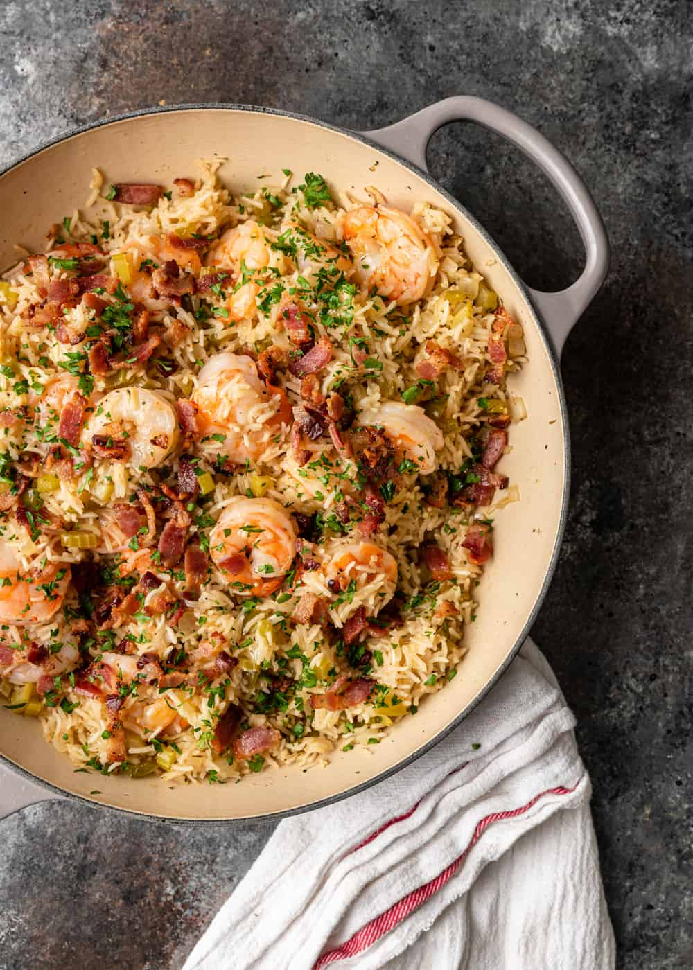 overhead of cajun shrimp in casserole pan with rice, herbs and vegetables