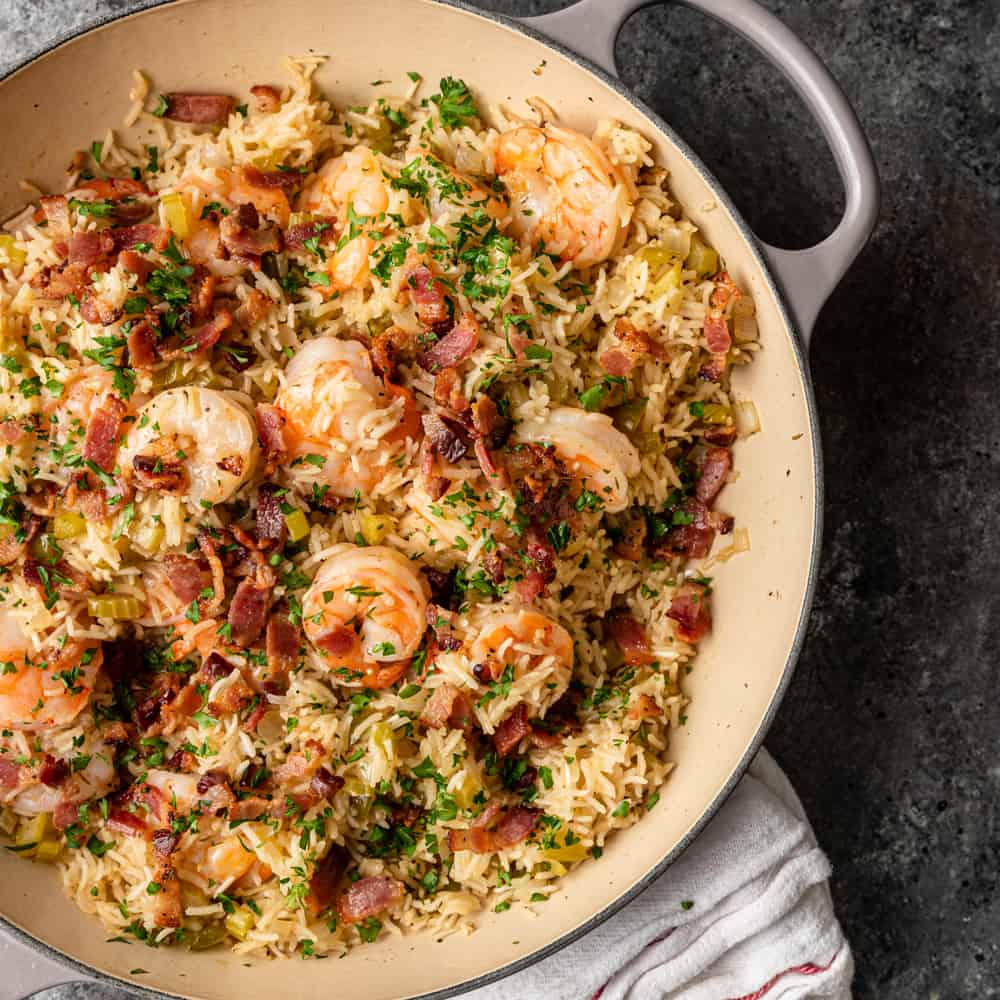 overhead of skillet shrimp recipe: shrimp with bacon, rice and herbs in a skillet