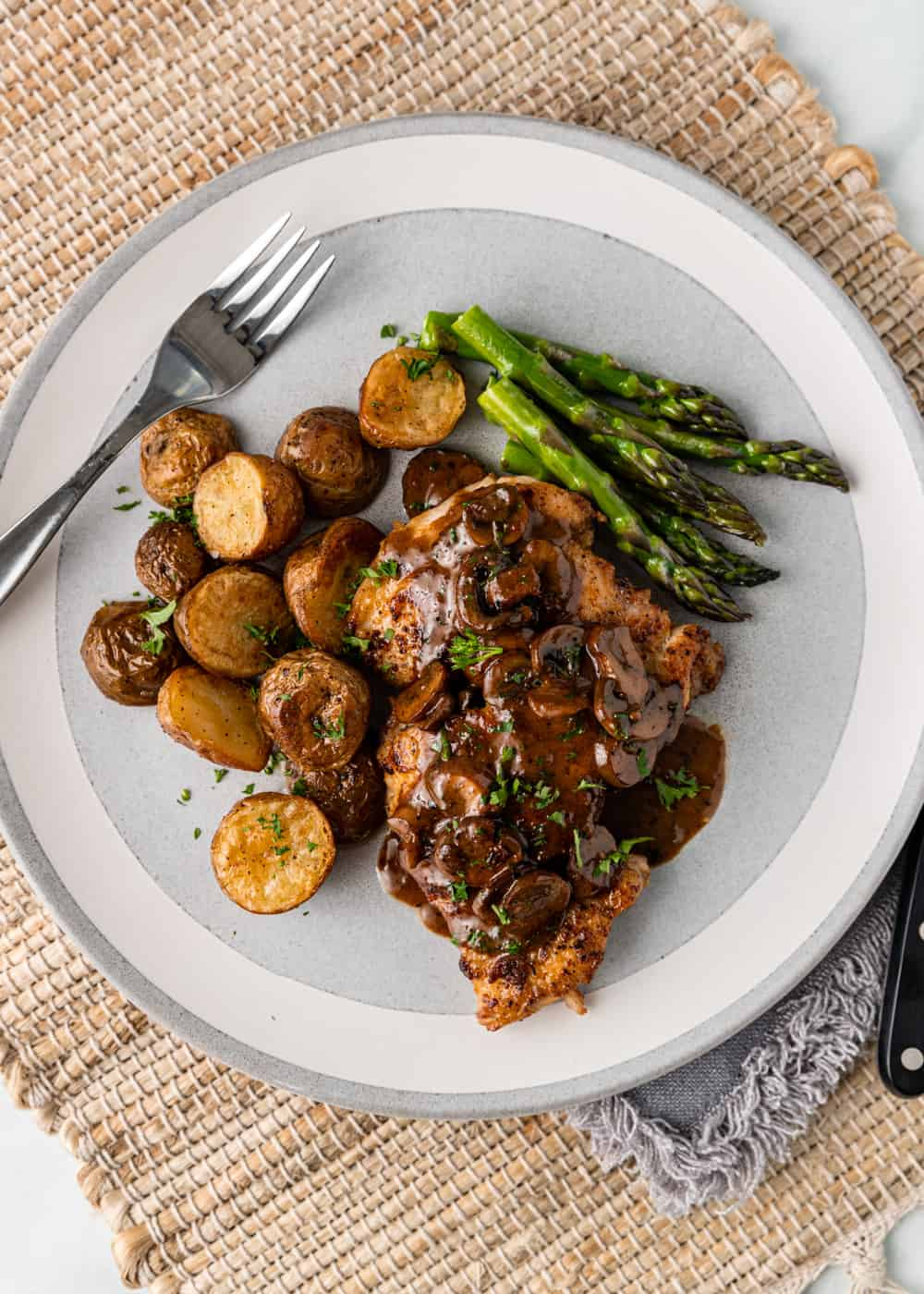 overhead photo: plated dinner of pan seared chicken thighs with roasted potatoes and asparagus