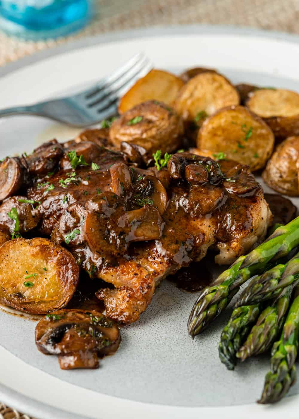 hearty chicken dinner on plate with mushroom gravy and asparagus