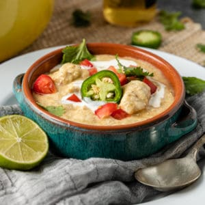 bowl of creamy chicken tortilla soup garnished with jalapeno slices and diced chicken breast