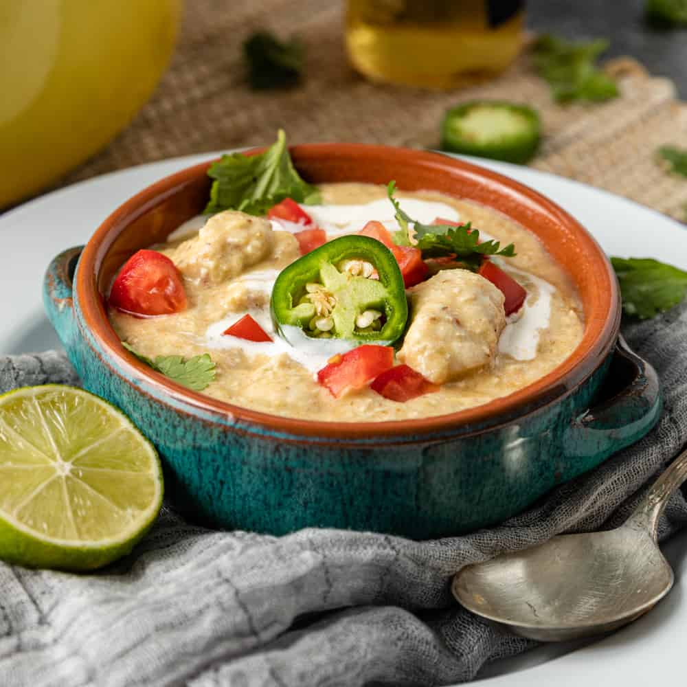 bowl of creamy chicken tortilla soup garnished with jalapeno slices and diced chicken pieces