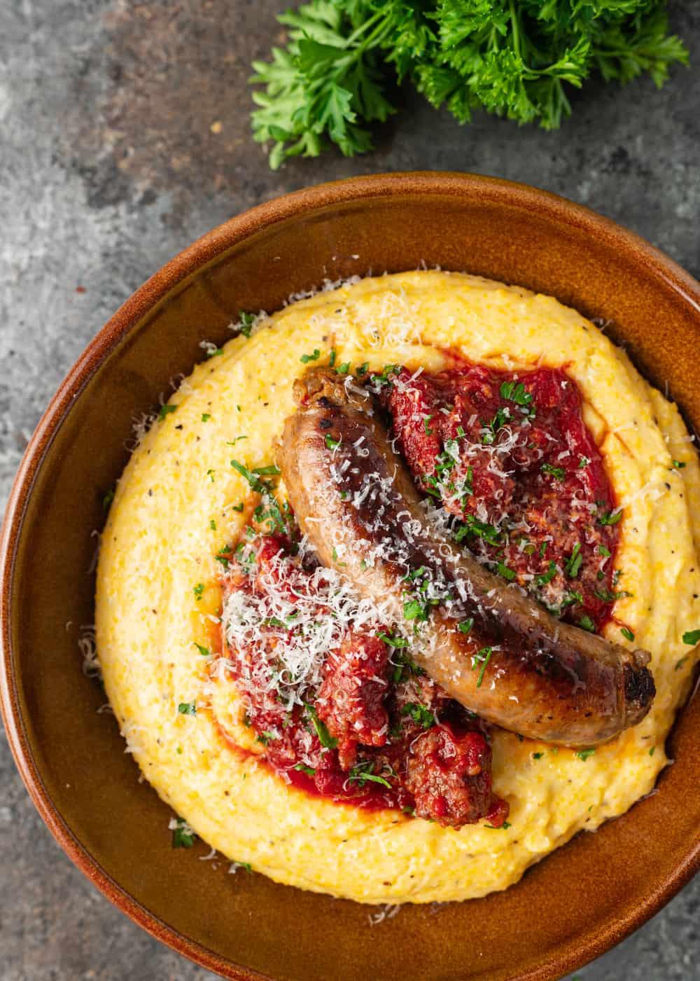 overhead image: sausage link on top of creamy polenta with ragu sauce