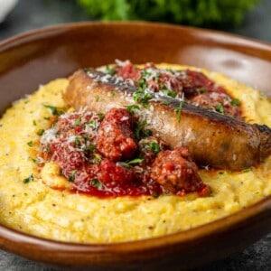 Italian sausage ragu served over plate of creamy parmesan polenta