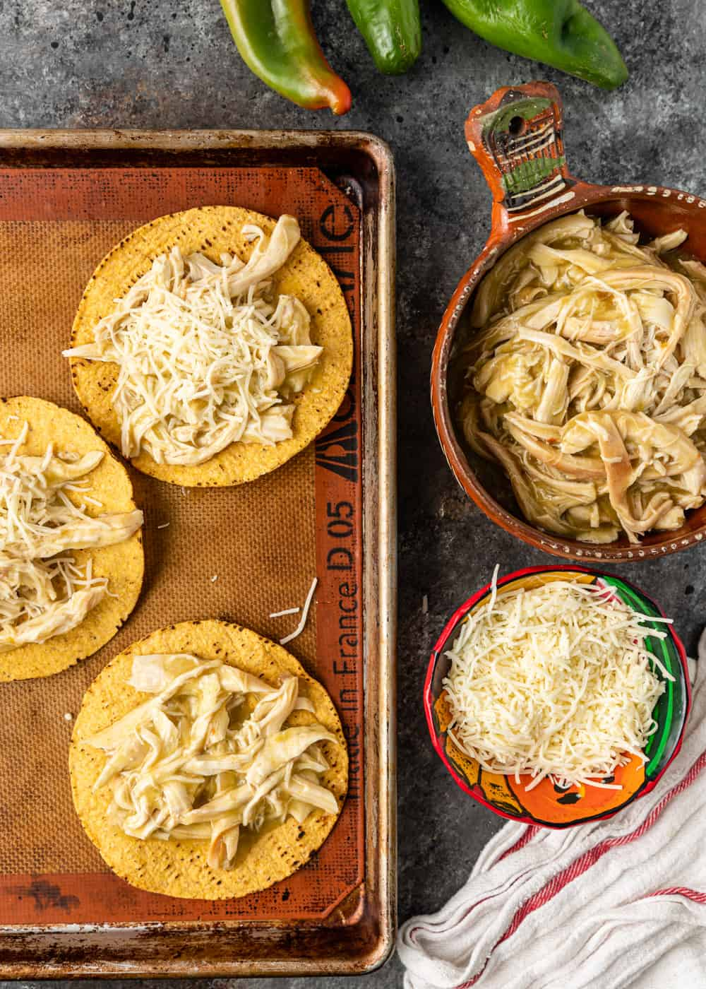 assembling a chicken tostada recipe with shredded chicken and shredded cheese