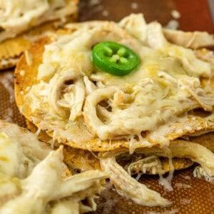 shredded chicken tostadas garnished with jalapeno