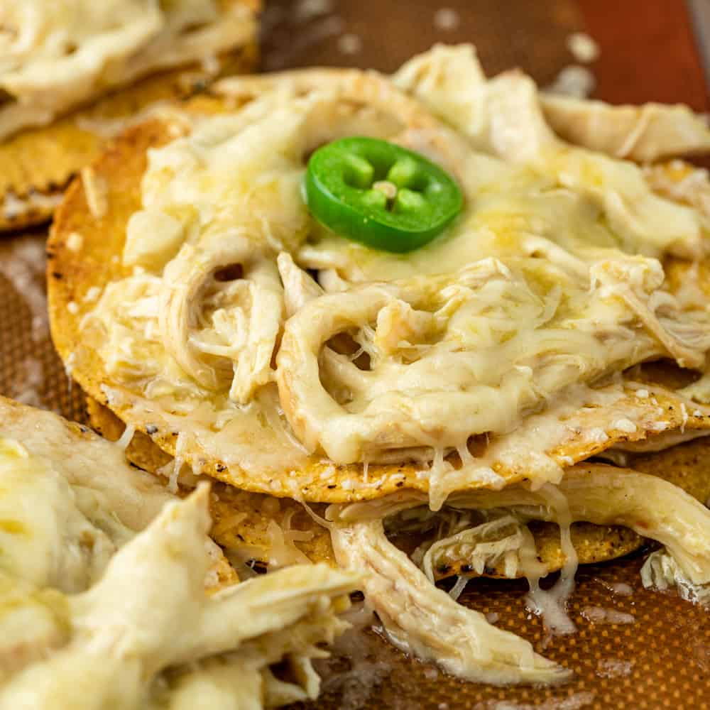close up: cheesy shredded chicken tostadas garnished with jalapeno