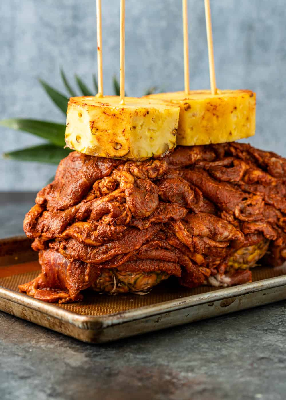 pile of juicy oven roasted Mexican-spiced pork on sheet pan with large pieces of fresh pineapple skewered on top