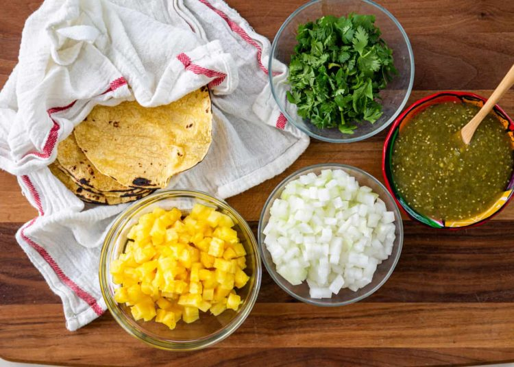 bowls of diced pineapple, diced onion, fresh cilantro, and green chili sauce next to corn tortillas wrapped in a white kitchen towel