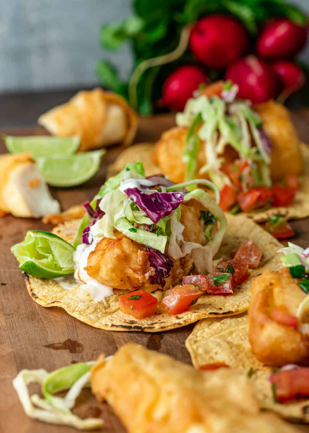 side view of seafood taco dinner on wooden board