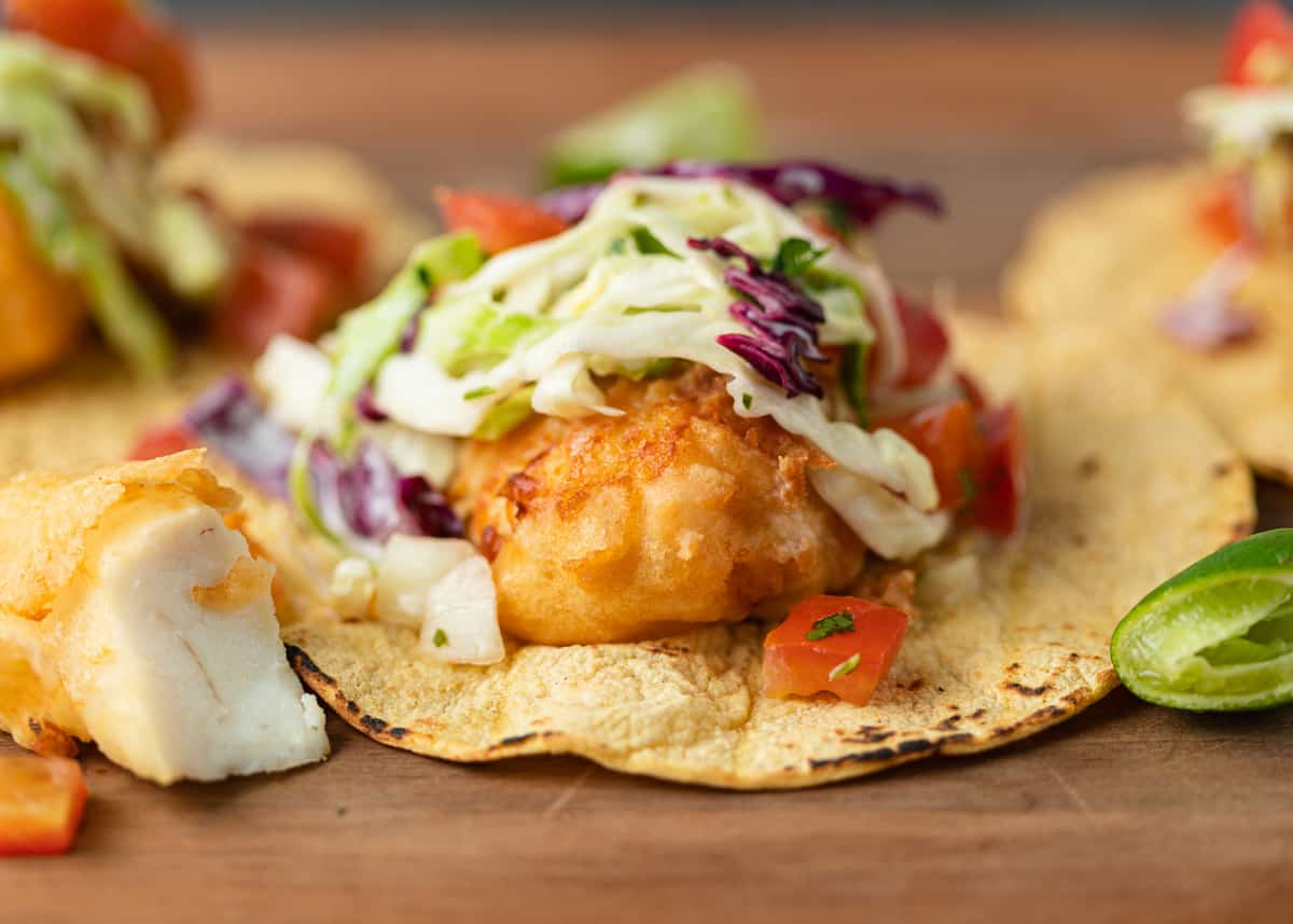 baja style fish taco on corn tortilla topped with purple slaw