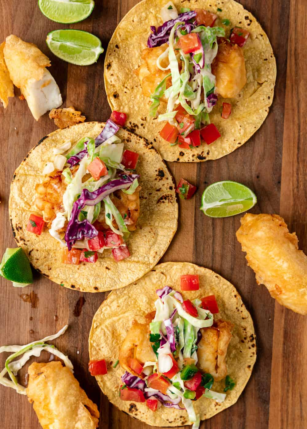 overhead image: 3 open face battered fish tacos on a wooden serving board