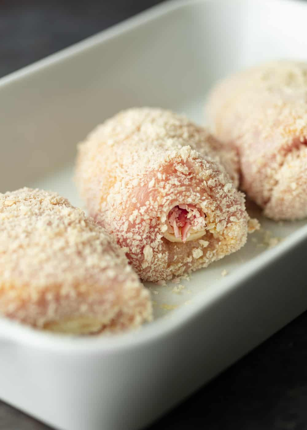 3 raw chicken breasts rolled up with ham and cheese, coated in panko breadcrumbs