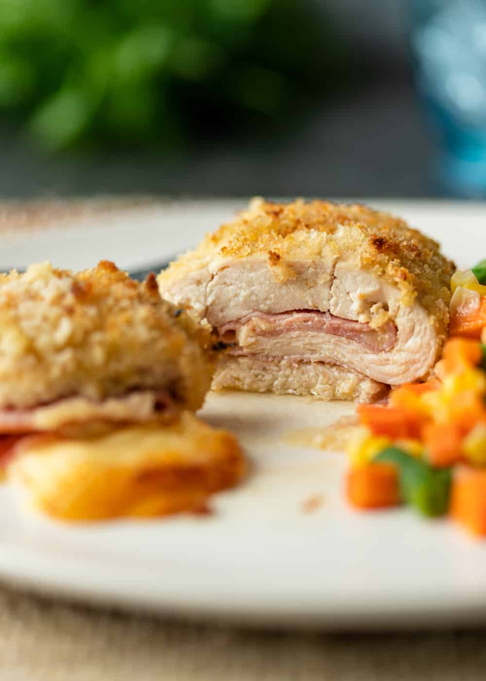 side view of baked chicken breast stuffed with ham and cheese on a dinner plate with mixed veggies