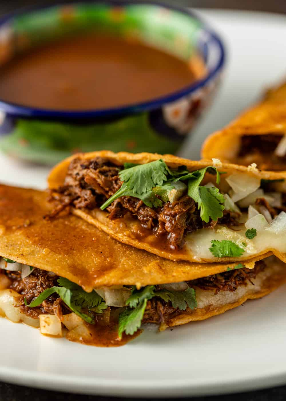 close up of a juicy sauced birria taco with melted cheese and a bowl of consomme