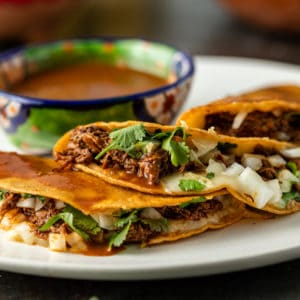 A plate of Birria Tacos and small bowl of consumme