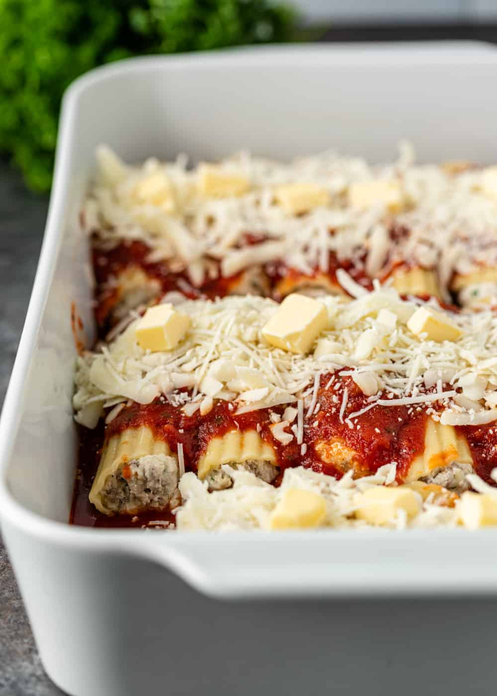 butter and cheese on top of stuffed manicotti in pan