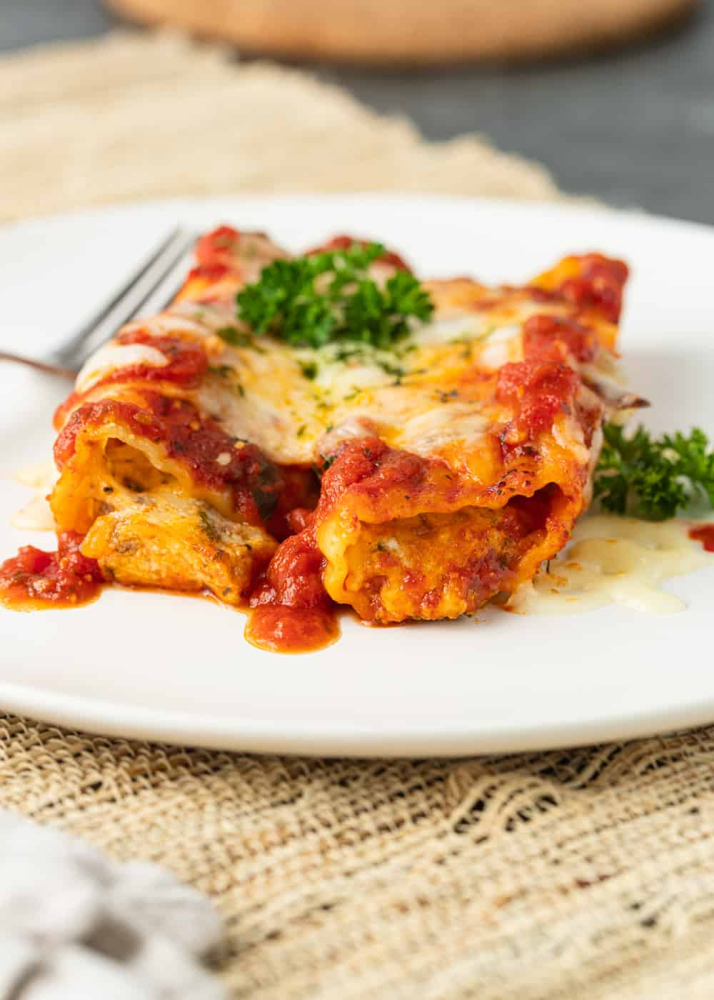 two manicotti with sauce and melted cheese on white plate